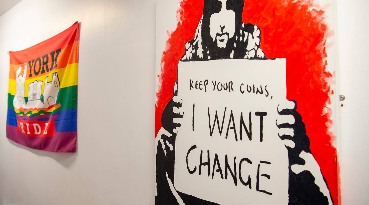 Street art depicting a homeless person holding up a sign that says Keep your coins, I want change